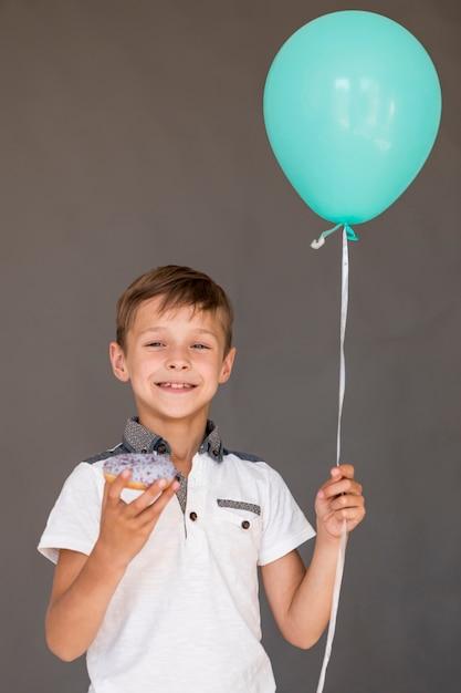 艶をかけられたドーナツと風船を持つ男の子 無料写真