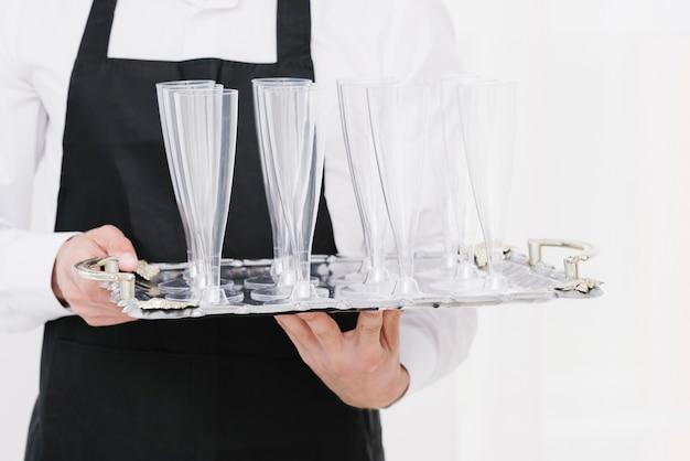 Официант держит пустые стаканы на подносе Бесплатные Фотографии
