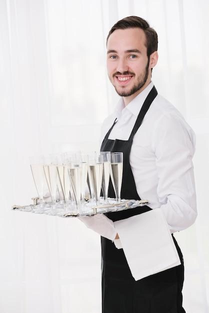 Элегантный официант подает бокалы для шампанского Бесплатные Фотографии