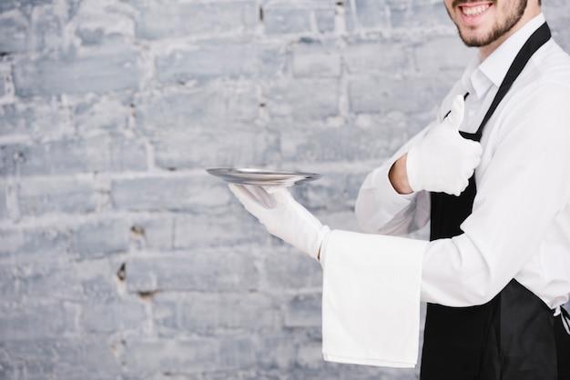 Молодой официант держит тарелку на кирпичном фоне Бесплатные Фотографии