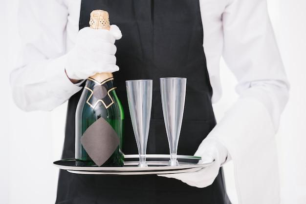 Официант в форме держит бутылку с бокалами Бесплатные Фотографии