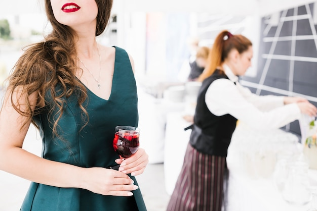 アルコールとガラスを保持している美しい女性 無料写真