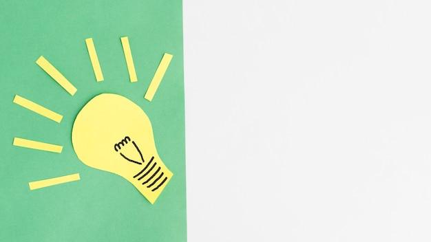 コピースペースと緑の背景の上の電球の黄色い紙の切り欠き 無料写真