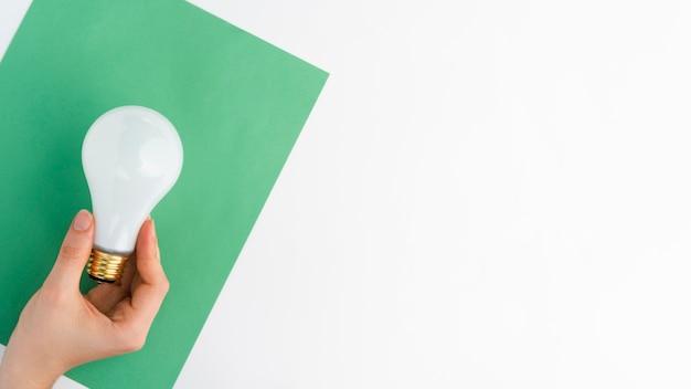 白い背景に、緑の紙の上に電球を持っている手のクローズアップ 無料写真