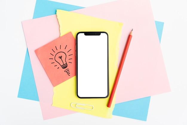 空の画面の携帯電話と白い背景の上のカラフルなクラフト紙の上の鉛筆 無料写真