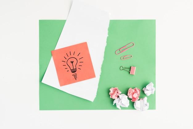 グリーンカード紙に描かれた電球とペーパークリップでしわくちゃの紙の立面図 無料写真