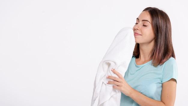 ミディアムショットの女性がきれいなタオルの臭いがする 無料写真