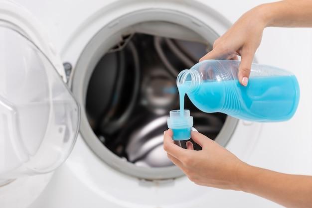 クローズアップ女性のキャップに洗剤を注ぐ 無料写真