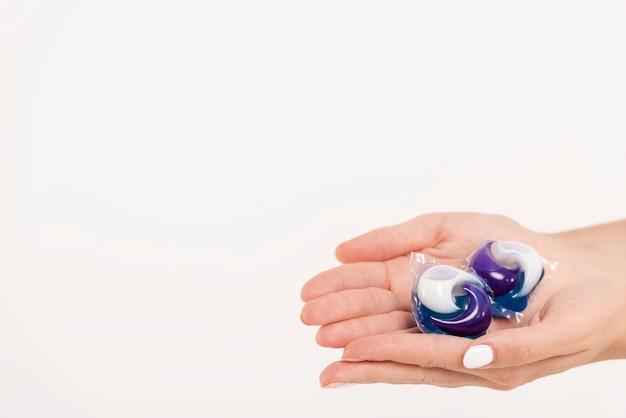 Крупным планом женщина, держащая стиральные таблетки Бесплатные Фотографии