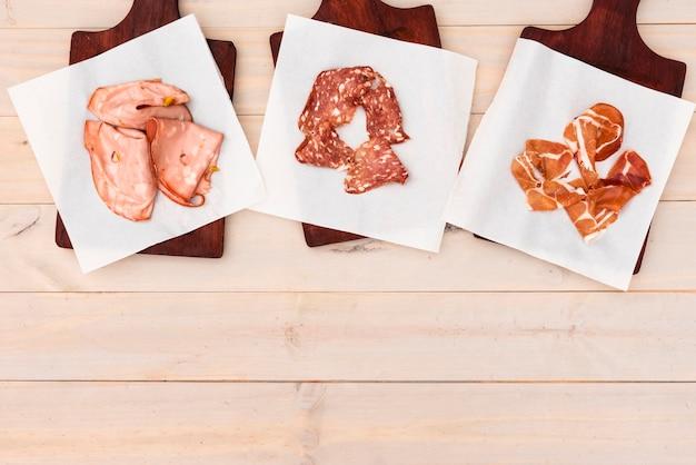 別のイタリアのハムとテーブルの上のまな板の上のサラミ 無料写真