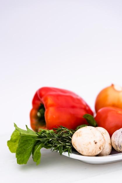 白い背景の白いトレイに新鮮な有機野菜 無料写真