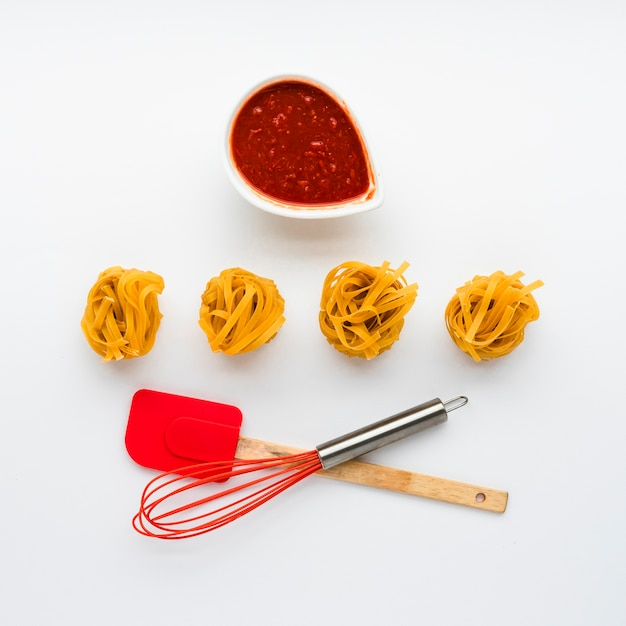 Сырые тальятелле паста и томатный соус с кухонной утварью на белом фоне Бесплатные Фотографии