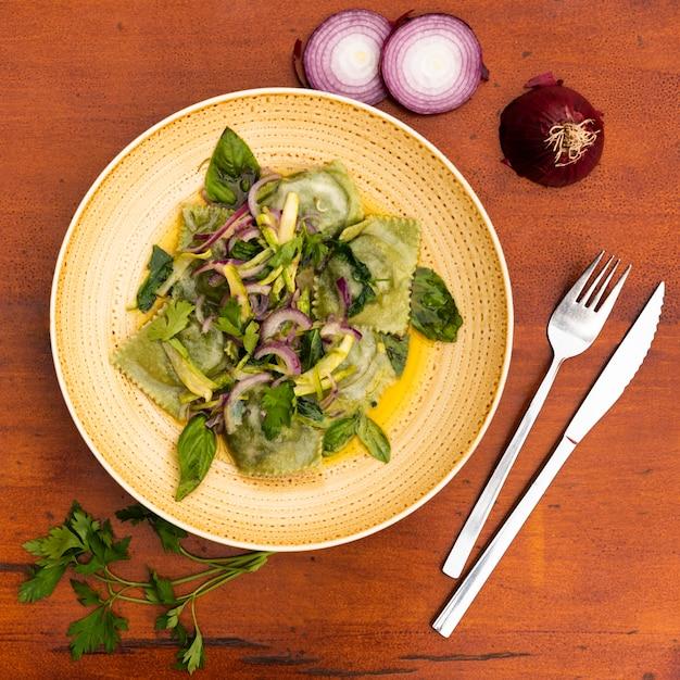 タマネギとバジルと緑のラビオリのトップビュー葉木製テーブル 無料写真