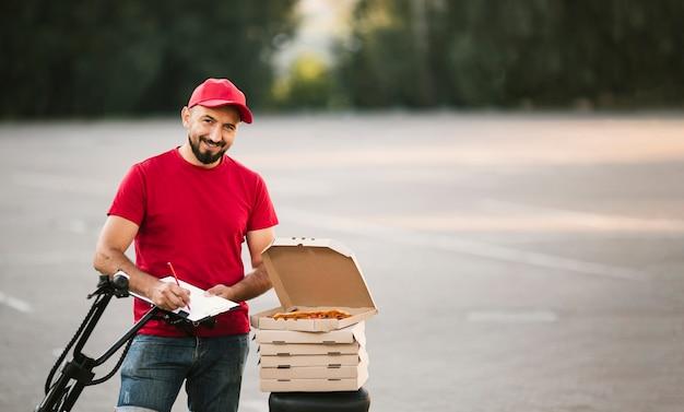 ピザの執筆とミディアムショットスマイリー男 無料写真