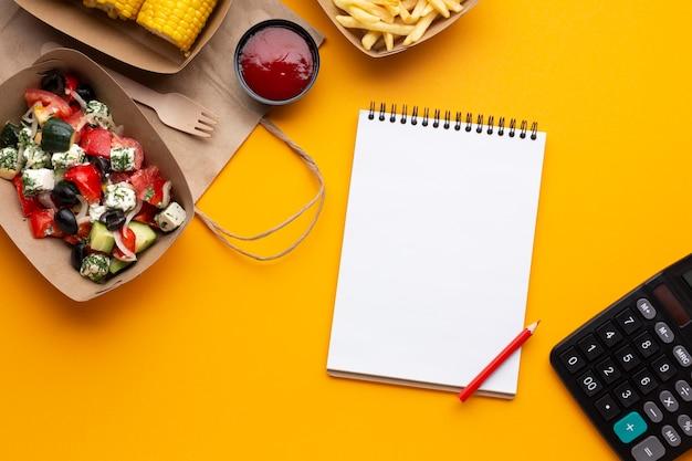 黄色の背景上のノートブックとトップビュー食品 無料写真