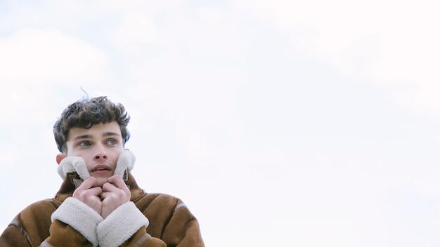 コピースペース付きジャケットで耳を覆う若い男 無料写真