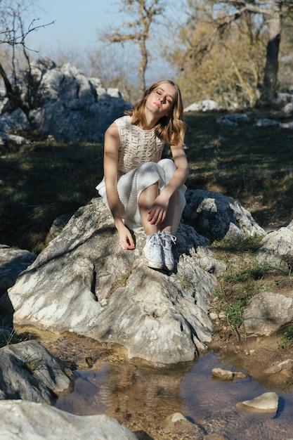 Длинный выстрел женщина сидит на скале Бесплатные Фотографии