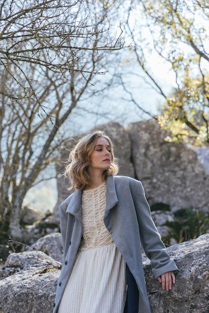 岩を見つめて若い女性 無料写真