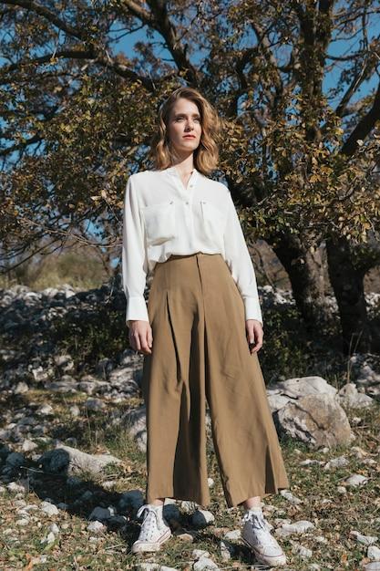 カジュアルな服装でロングショット立っている女性 無料写真