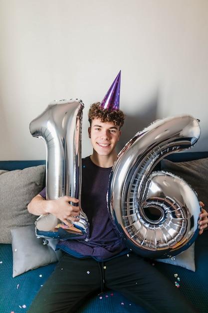 Счастливый подросток держит воздушные шары на день рождения Бесплатные Фотографии