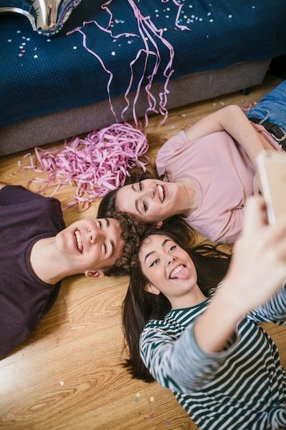 Высокий угол друзей, принимающих селфи на полу Бесплатные Фотографии