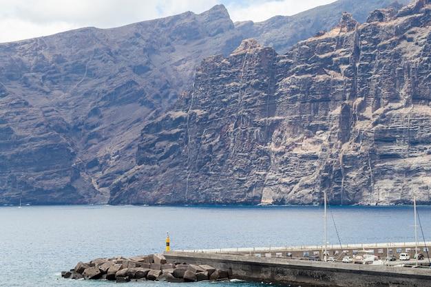 Гигантские скалы с морем в солнечный день Бесплатные Фотографии