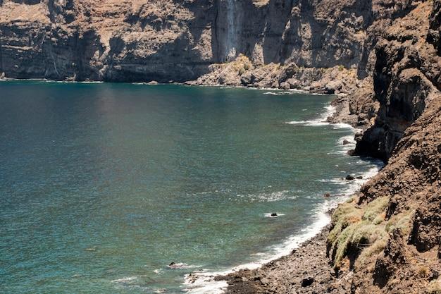 背景に崖と澄んだ青い水 無料写真