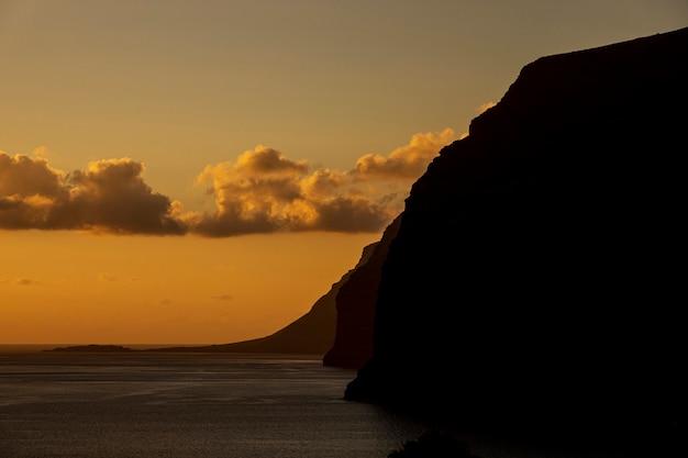 Высокий утес на берегу моря на закате Бесплатные Фотографии