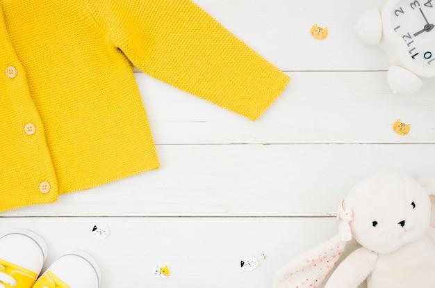 Плоская лежала детская одежда с деревянным фоном Бесплатные Фотографии