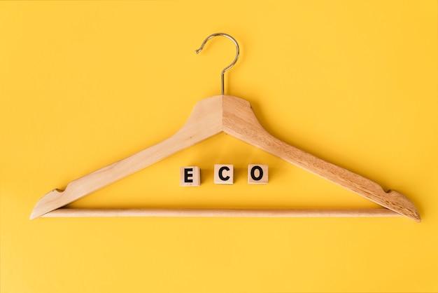 黄色の背景のトップビュー木製ハンガー 無料写真