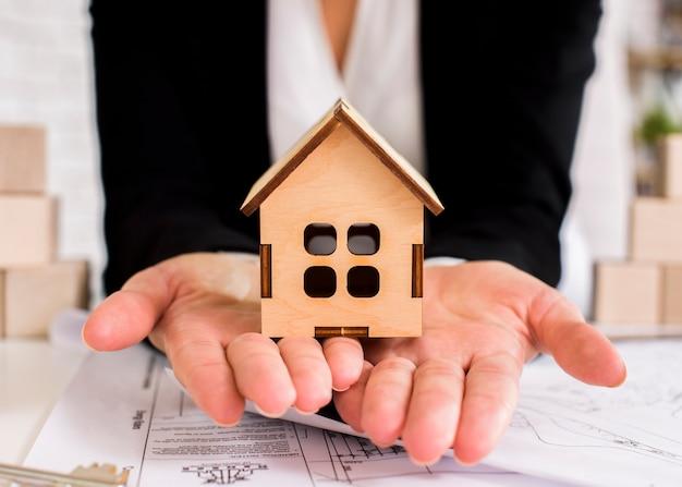 女性の手にクローズアップ木造住宅 無料写真