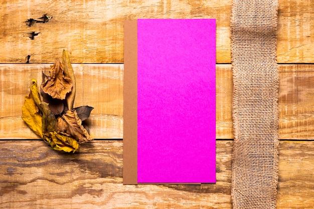 フラットレイアウトの封筒と木製の背景を持つ黄麻布 無料写真