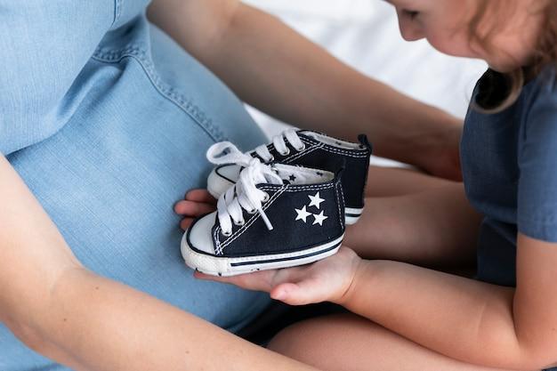 小さな女の子が彼女の弟の靴をチェック 無料写真
