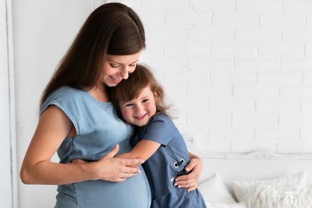 彼女の妊娠中の母親を抱いて娘 無料写真
