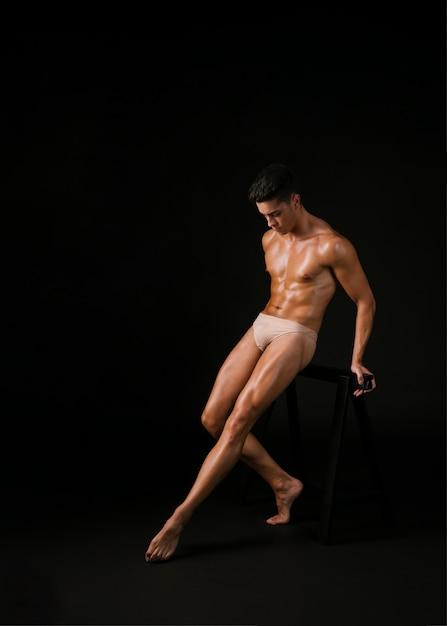 Мускулистая танцовщица опирается на барре Бесплатные Фотографии