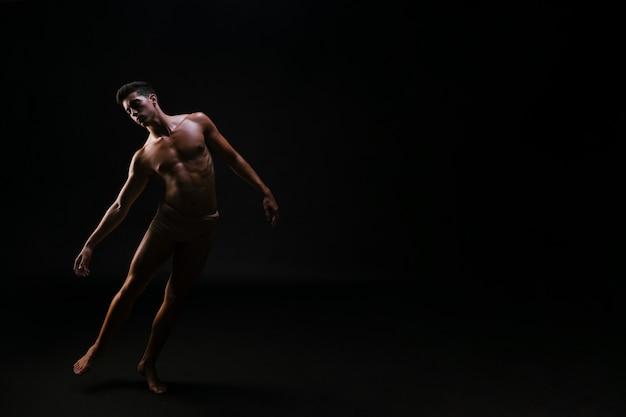 黒の背景に立っている裸の運動曲がった男 無料写真