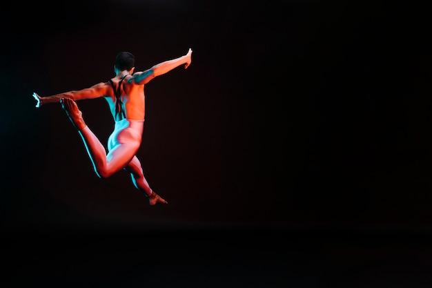認識できないバレエダンサーが腕を広げてジャンプし、分割を行う 無料写真