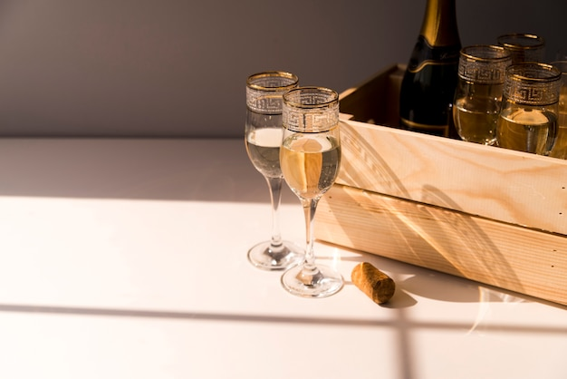 白いテーブルの上の木製の箱でシャンパンとワインのグラス 無料写真