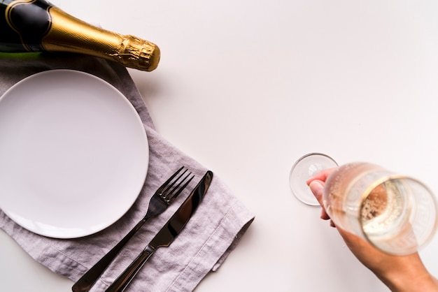 Вид сверху человеческой руки положить бокал с шампанским возле пустой белой тарелке на простой фон Бесплатные Фотографии