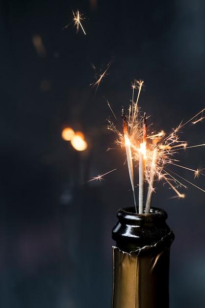 暗い背景にワインの瓶でバーリング線香花火のクローズアップ 無料写真