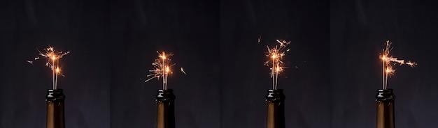 Ряд бутылку шампанского с огнем спарклер черном фоне Бесплатные Фотографии