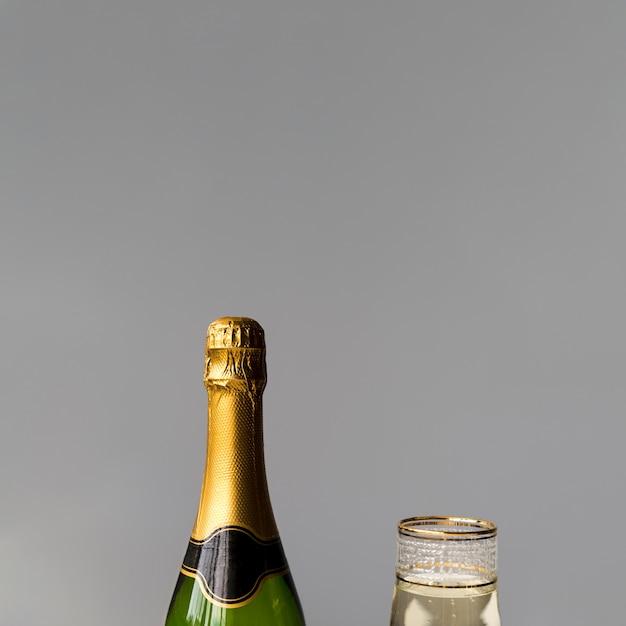 新しいシャンパンボトルと灰色の壁にガラスのクローズアップ 無料写真