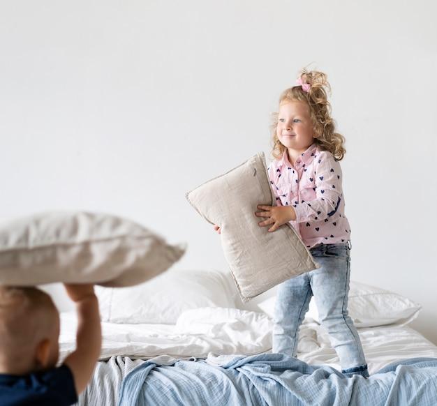 Полный выстрел девушка, стоя в спальне с подушкой Бесплатные Фотографии