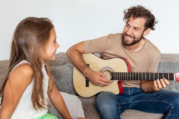 ギターを弾く父のミディアムショット 無料写真