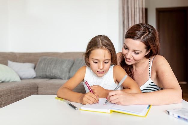 Мать помогает дочери делать домашнее задание Бесплатные Фотографии