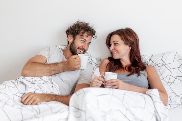 かわいいカップルがベッドの中でコーヒーを飲む 無料写真