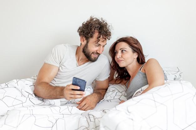 笑っているベッドの中でカップル 無料写真