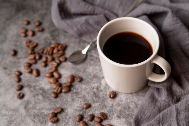 Чашка кофе с кофейными зернами и ложкой Бесплатные Фотографии