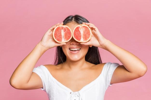 グレープフルーツの半分で彼女の目を覆っている女性 無料写真