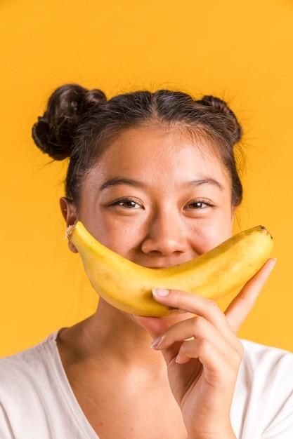 Женщина держит банан в виде улыбающейся фигуры Бесплатные Фотографии